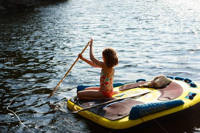 Girl paddling on a raft