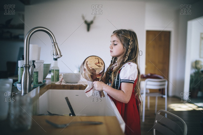 A girl dries a glass pot