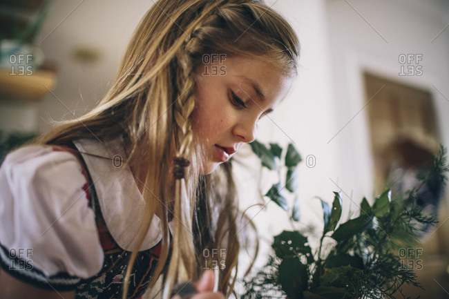 A little girl leans over plants