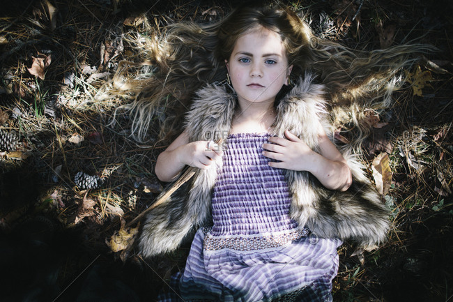 A girl lays outside in pine needles
