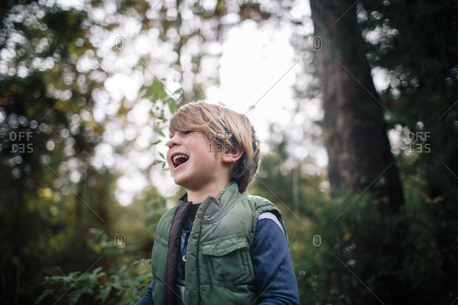 A boy laughs in the forest