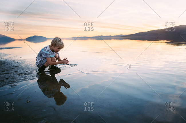 Boy playing on the shore at sunset