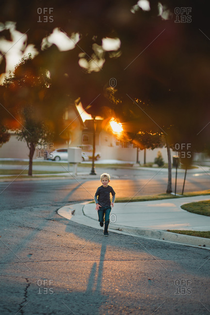 Boy running on the street at sunset