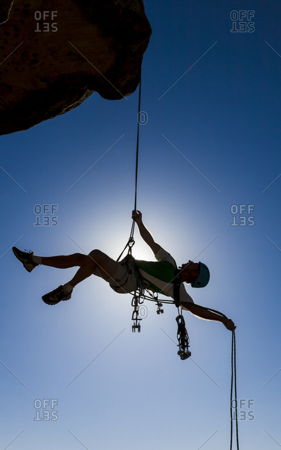 Climber rappels from the summit of a challenging cliff