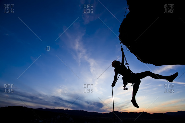 Silhouette of climber hanging from a challenging cliff