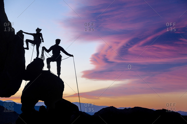 People climbing up a mountain at sunset