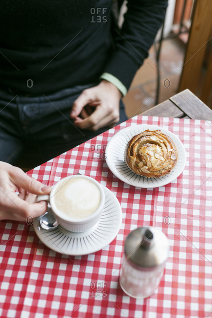 Man having a cappuccino with a Danish roll
