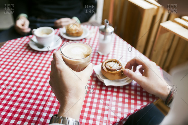 Person having a cappuccino with a Danish roll
