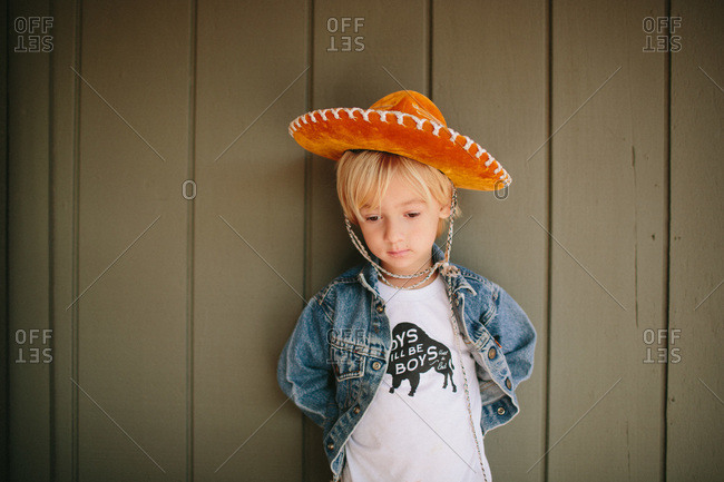 Little boy leaning against wall in mexican hat