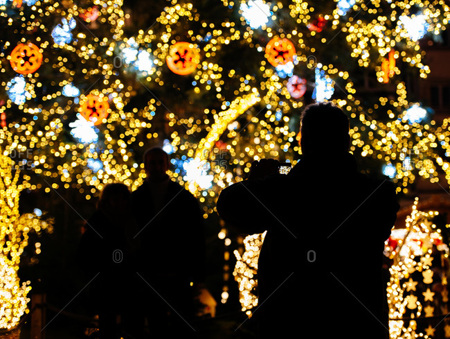 Man taking photo of friends posing at Christmas tree in Strasbourg