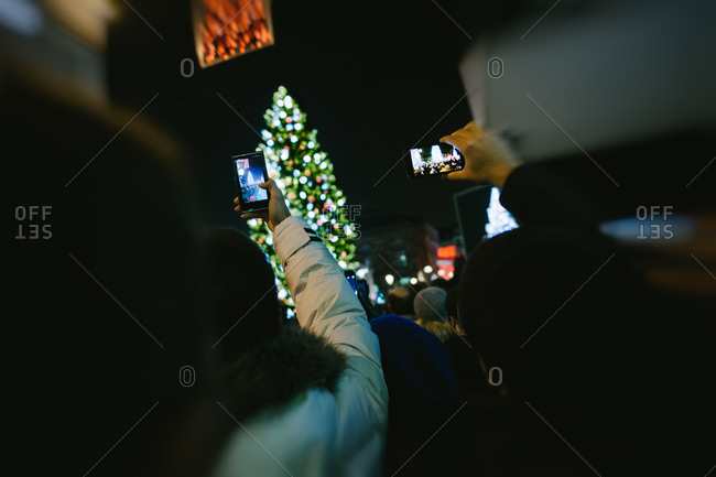 People taking pictures of a lighted Christmas tree with their smartphones
