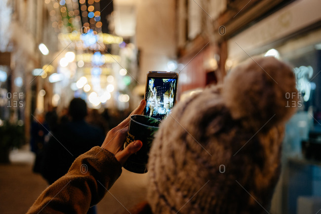 Woman in hat photographing Christmas street scene in Strasbourg, France