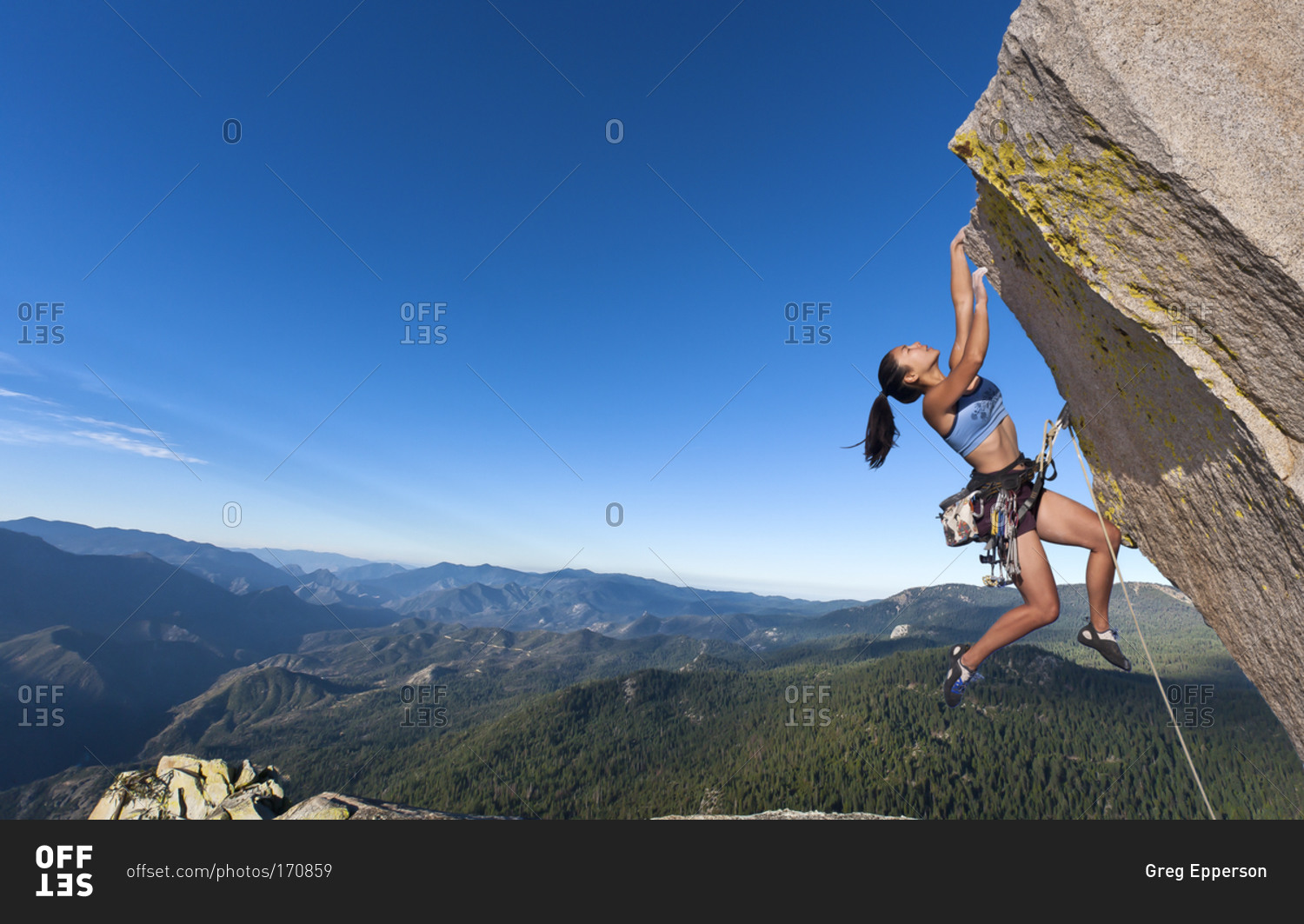 Woman hanging from a cliff stock photo - OFFSET
