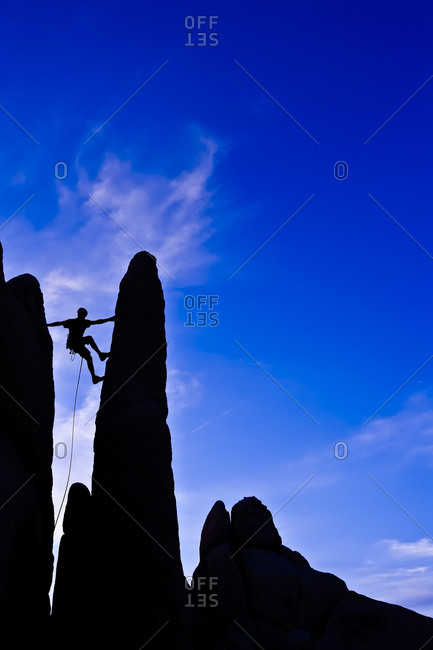 Silhouette of man climbing up a rock formation