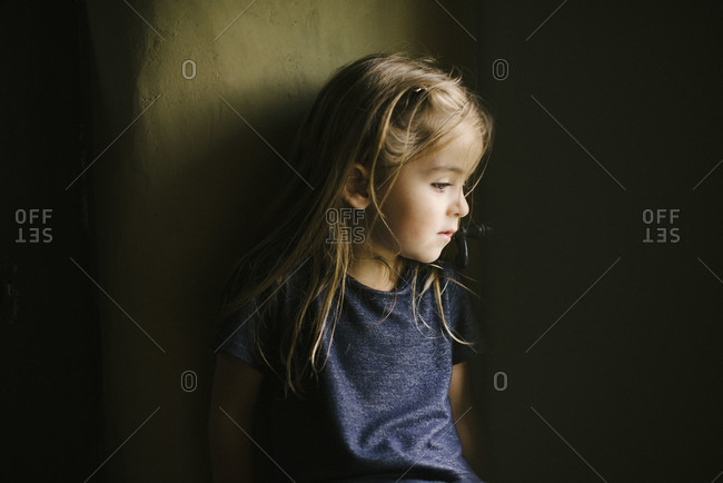Young girl leaning against a stucco wall
