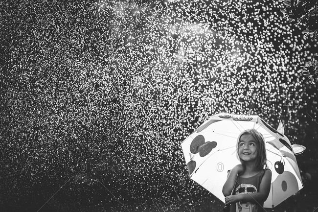 Girl with cow umbrella enjoying a rain shower