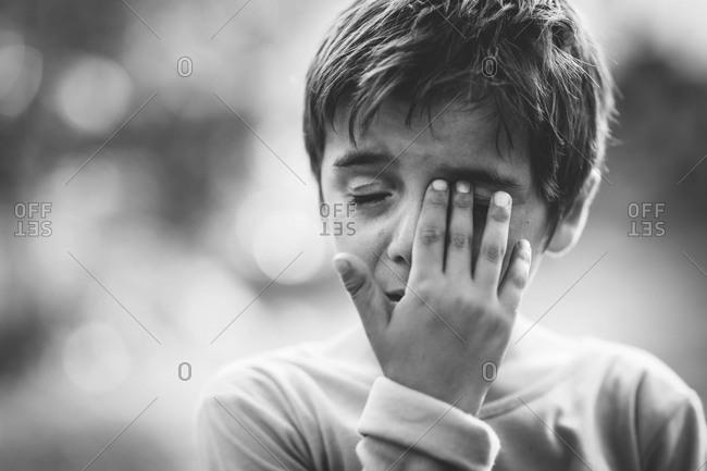 Upset boy wiping his eye