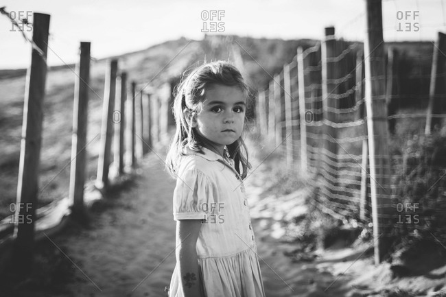 Girl in field between to fence rows