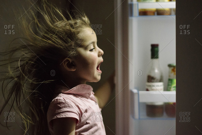 Girl being hit with a blast of cold air while opening a refrigerator