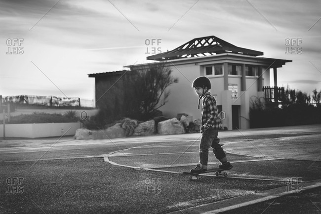 Boy skateboarding in the street of a beach town