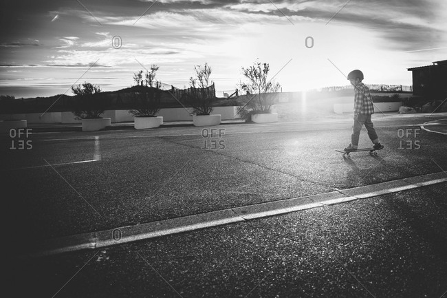 Boy skateboarding in the street of a coastal town