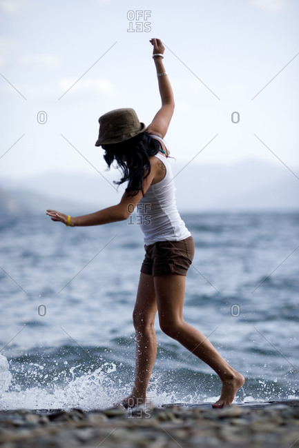 20 year old woman walking along shore of lake with her arms in the air for balance
