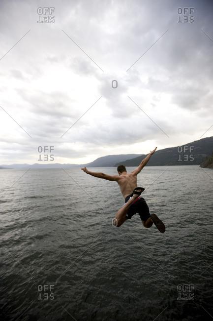 20 year old man jumping into a lake