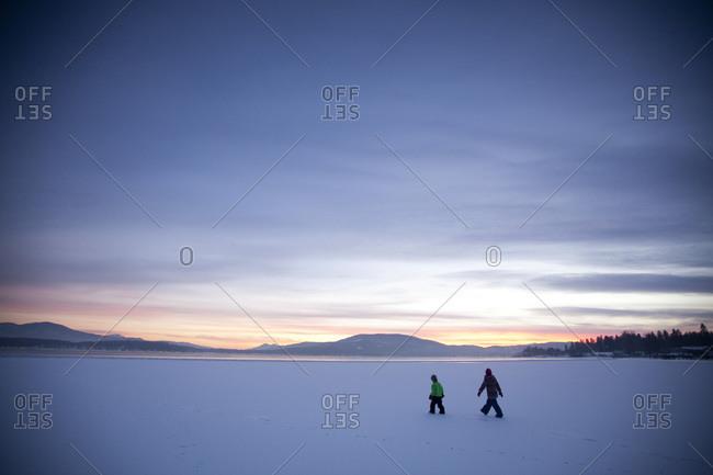 Two little kids walking on the ice