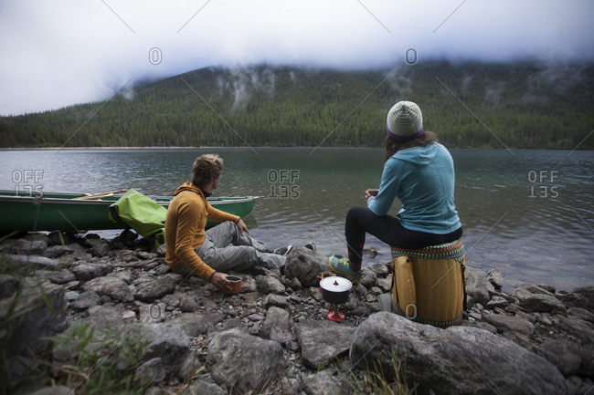 Man and woman hanging out on the edge of a mountain lake