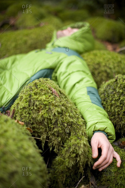 Man laying in mossy rocks