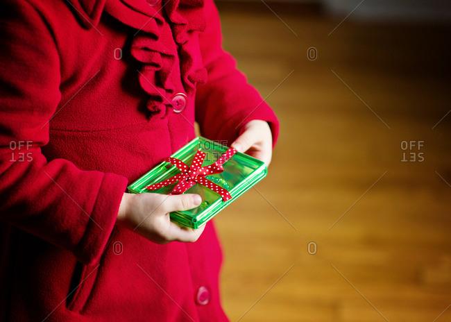 A little girl holds a present