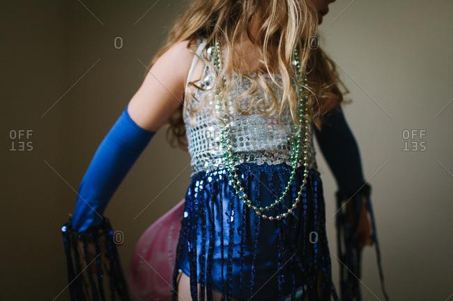 A little girl playing dress up
