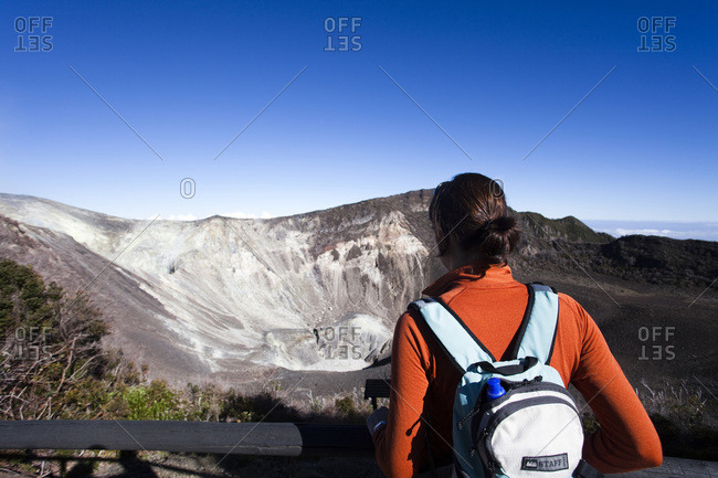 A young girl looks at an active volcano