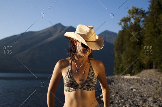 A young woman, wearing a cowboy hat, enjoys the calm, blue waters of a lake as the sun sets near mountains in the distance