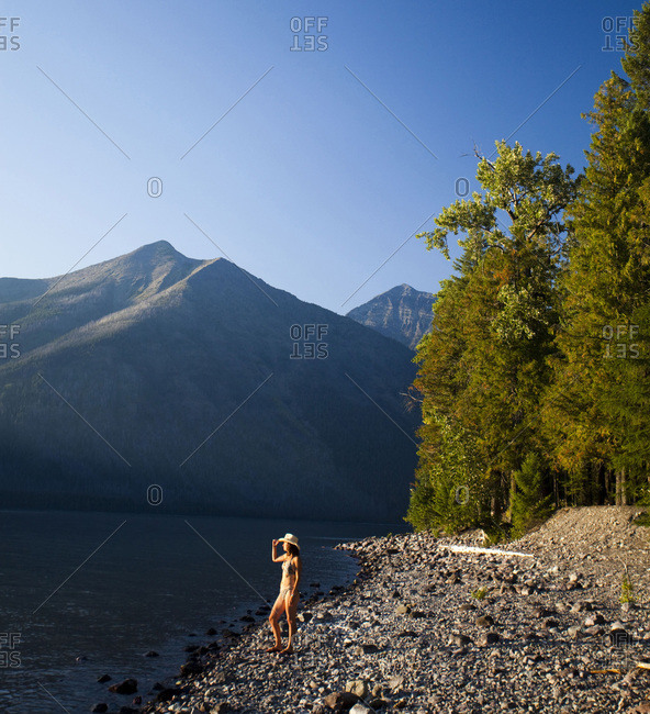 A young woman stands on the rocky shore of a clear lake as the sun set behind distance mountains