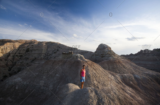 A young woman on a narrow ridge in Badlands National Park, South Dakota
