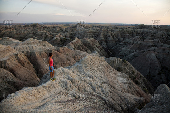 A young woman stands on top of a ridge with the dramatic Badlands National Park, South Dakota in the background