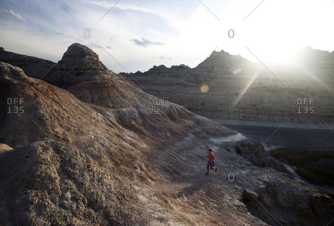 A young woman, wearing pink, runs along an unmarked trail in Badlands National Park at sunset, South Dakota