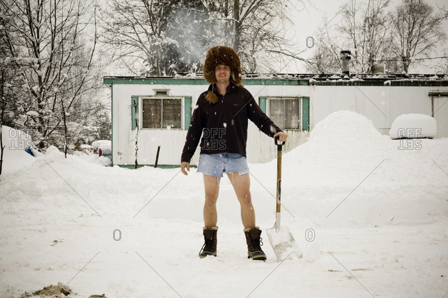 A portrait of a young man wearing a large, furry hat and jean shorts while holding a shovel