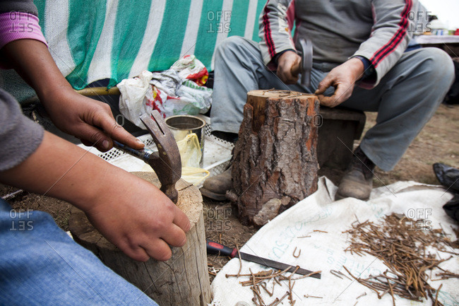 Two local men straighten out piles of nails, using hammers to bang them against tree stumps, in the after math of the Chilean earthquake that struck in early 2010