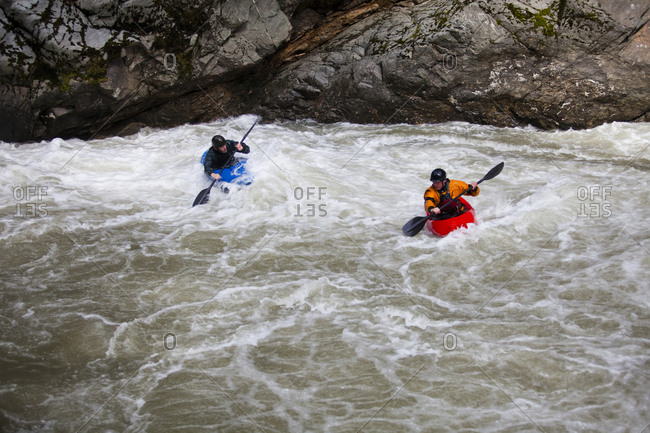 Two kayakers carry their boats along a rocky shore at the takeout after a 6 mile run on a dangerous river