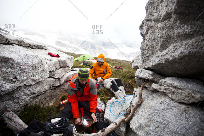 Two climbers prepare food while sitting between rocks hoping to avoid the wet conditions