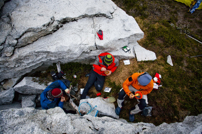 Three climbers eat dehydrated food between rocks hoping to avoid the wet conditions