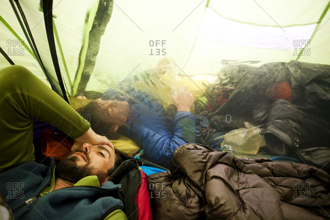 A climber rubs his head after a long day navigating through whiteout conditions while attempting to summit a mountain Another climber sleeps in the vestibule of the tent trying to avoid the rain