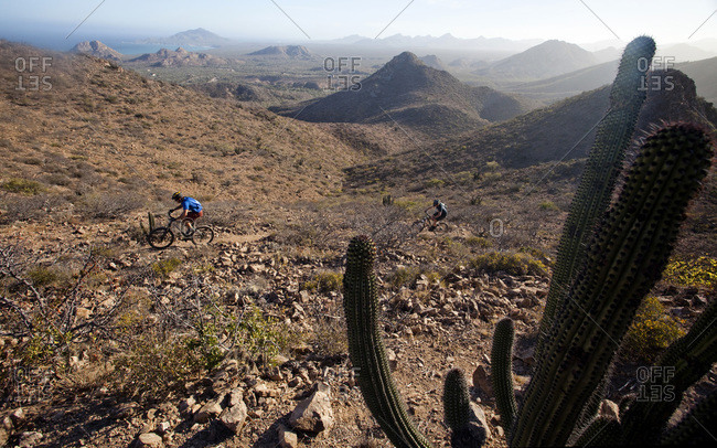 A mountain biker on a dirt trail surrounded by mountains and the occasional view of the ocean in the distance