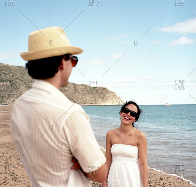 A woman smiles at her boyfriend as she walks down the beach on a sunny afternoon wearing a white sun dress