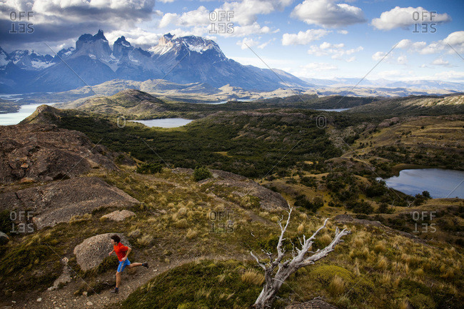 A runner follows a trail on a ridgeline with dramatic views in the background