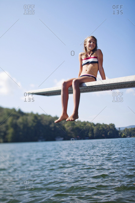 A young girl sits on the edge of a diving board on a sunny afternoon in her swimsuit