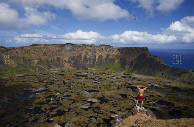 A young man stands on a rocky outcropping overlooking the ocean and a crater below on the world's most remote island