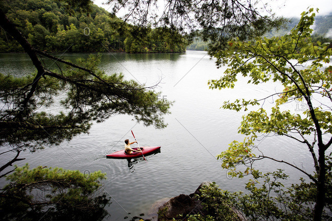 A man floats along in a kayak on a calm, rainy day on a lake with a green, lush background